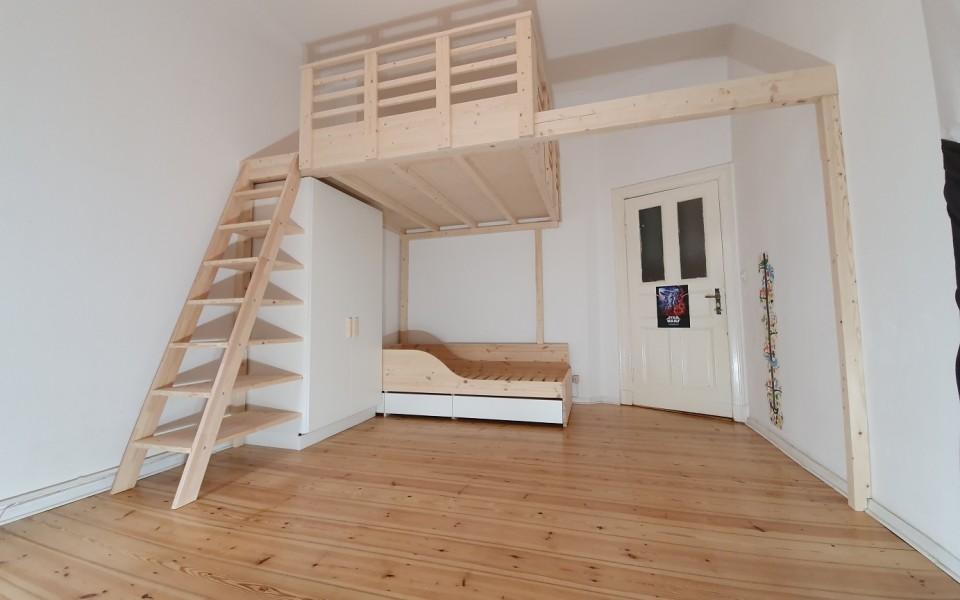 Hier sehen sie ein Menke-Schwebe-Bett ohne Eckpfosten im Raum, getragen von einem sehr stabilen Brettschichtträger. Ein Vollholzbett in Natur geschliffen mit einem integrierten Kleiderschrank, Leiterregalsystem sowie einem Kinderbett mit zwei Schubkästen.